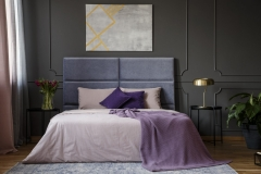 Violet blanket on the bed in pastel bedroom interior with grey poster on grey wall with molding
