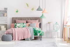 White and pink bedroom interior with leaves drawings hanging above a cozy bed with knit blankets